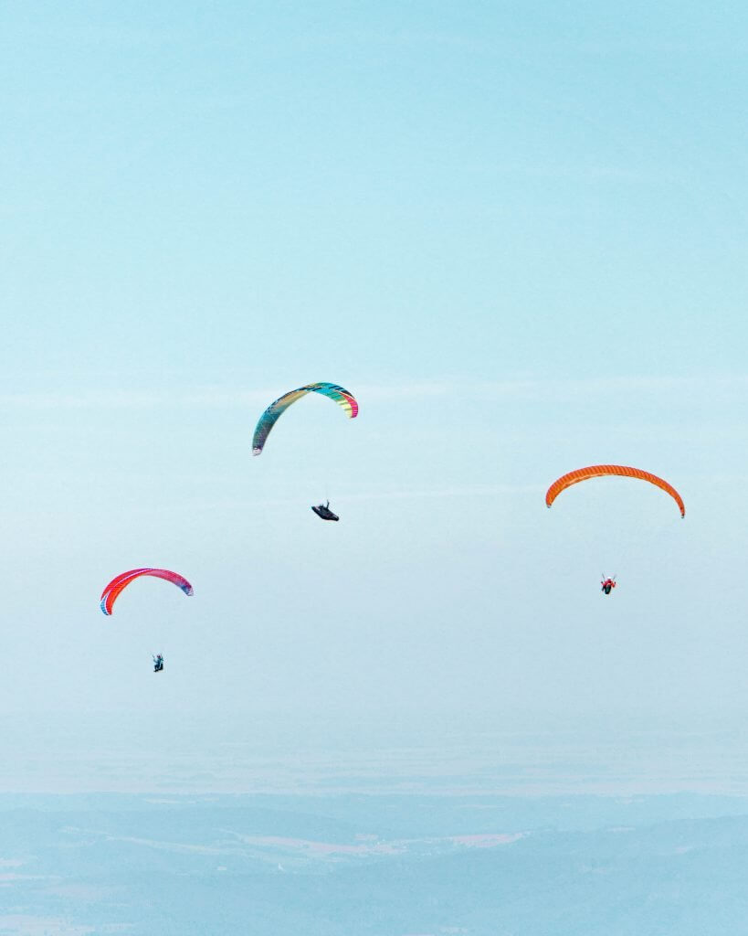 Three paragliders in the sky.