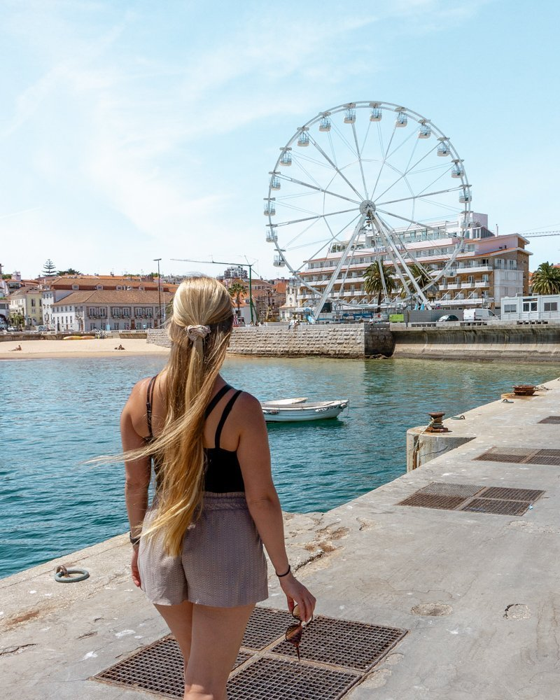 Jo exploring Cascais and a Ferris wheel in the background.
