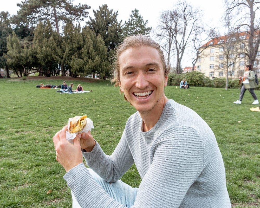 Dom eating a Mr Hotdog slider in Letna Park
